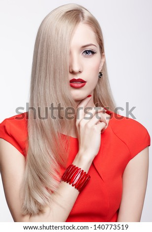 portrait of young beautiful long-haired blonde woman in red dress and bracelet with hair covering half of her face - stock photo