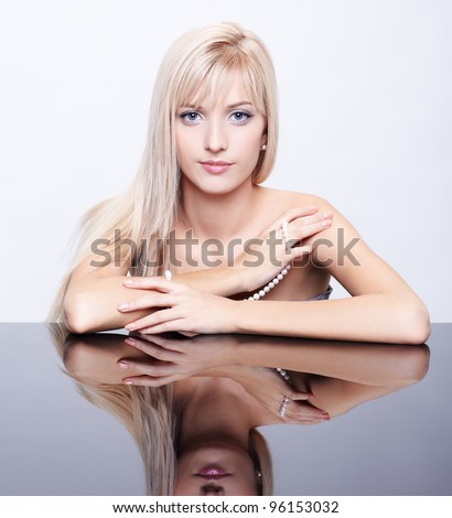 portrait of young beautiful long-haired blonde woman sitting at reflecting table with string of pearls in hands - stock photo