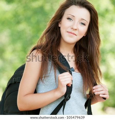 Portrait of young beautiful long-haired woman wearing grey t-shirt and black backpack at summer green park - stock photo
