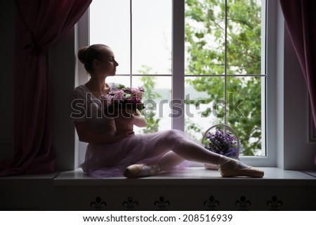 Portrait of young beautiful modern style ballet dancer sitting on windowsill, holding basket of flowers against window. Concept of romance and femininity and tenderness - stock photo