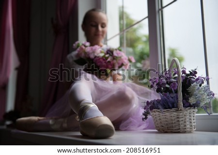 Portrait of young beautiful modern style ballet dancer sitting on windowsill with basket of flowers, selective focus. Concept of romance, tenderness - stock photo