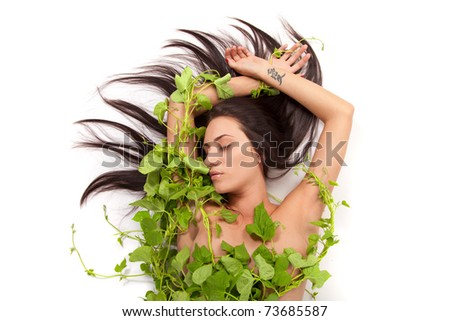 Portrait of young beautiful nude woman with green ivy leaves wrapped around her over white background - stock photo