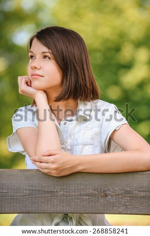 Portrait of young beautiful pensive dark-haired woman wearing white chemise at summer green park. - stock photo