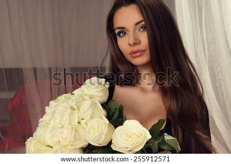 Portrait of young beautiful pretty woman holding big bouquet of white roses and smiling - stock photo