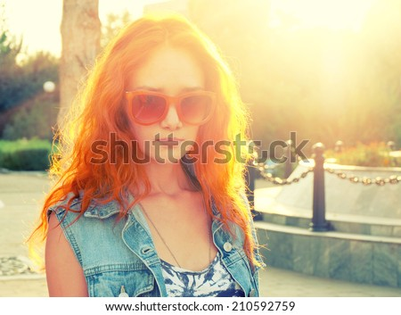 Portrait of young beautiful red haired and elegant stylish girl backlit with fence at background - stock photo