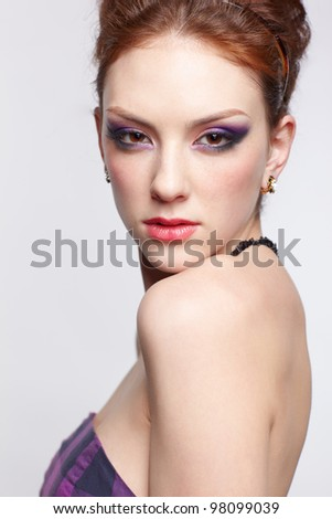 portrait of young beautiful red-haired woman looking over her shoulder - stock photo