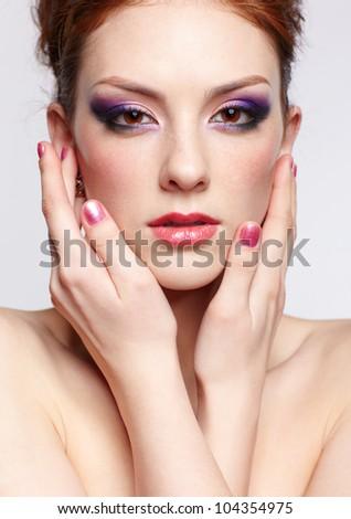 portrait of young beautiful red-haired woman touching face with manicured fingers on gray - stock photo