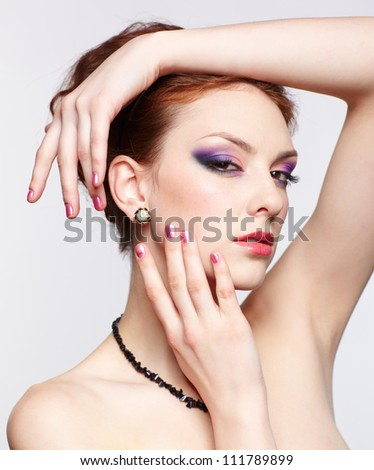 portrait of young beautiful redhead woman in beads and ear-rings touching her face with hands - stock photo