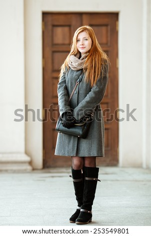 Portrait of young beautiful redhead woman wearing coat and scarf posing outdoors with architectural background - stock photo