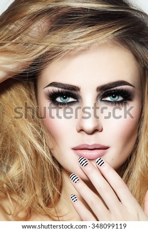 Portrait of young beautiful sexy girl with smoky eyes and stylish striped manicure - stock photo
