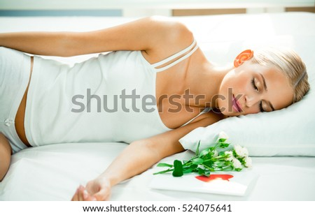 Portrait of young beautiful sleeping woman on bed with greeting valentines card and flowers. Love, romantic, relations theme concept.