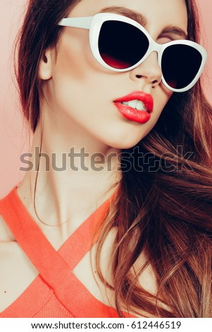 portrait of young beautiful slim woman in sexy dress with sensual lips in studio wearing sunglasses smiling and posing