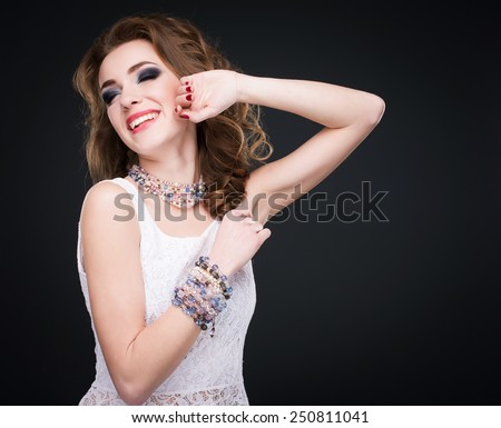 Portrait of young beautiful smiling brunette woman in jewelry standing over black background. Vogue style. Studio shot. Perfect hair and skin. - stock photo