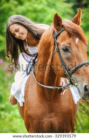 Portrait of young beautiful smiling brunette woman wearing white dress riding dark horse at summer green forest.