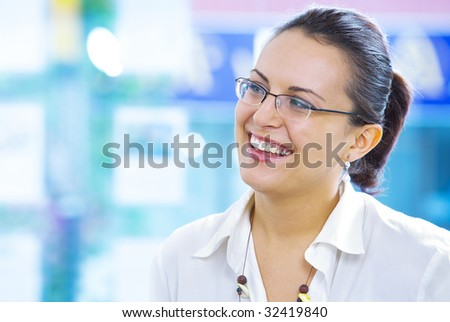 Portrait of young beautiful smiling  girl in office environment - stock photo