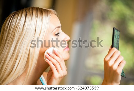 Portrait of young beautiful smiling woman applying creme at home. Beauty and fashion theme concept.