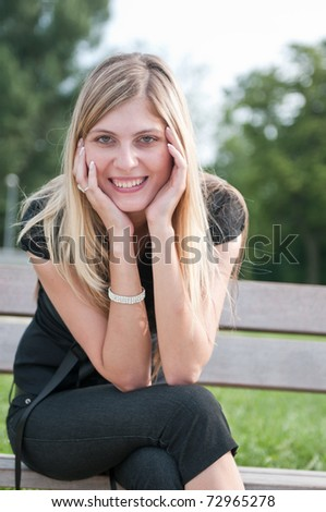 Portrait of young beautiful smiling woman siting on bench in park outside - stock photo