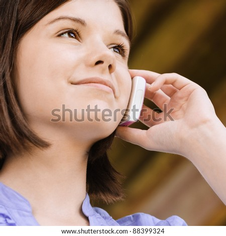 Portrait of young beautiful smiling woman talking on telephone. - stock photo