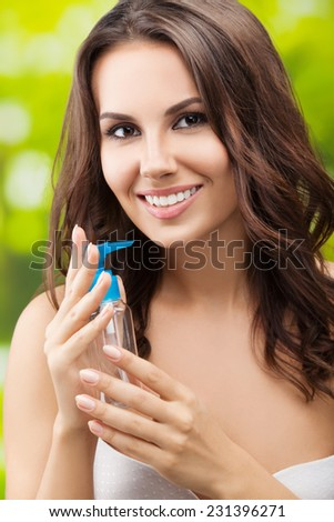 Portrait of young beautiful smiling woman with body lotion, outdoor - stock photo