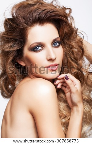 Portrait of young beautiful smiling woman with curly shaggy hair style with smoky eyes make-up on gray background - stock photo