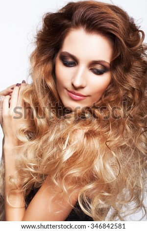 Portrait of young beautiful smiling woman with curly shaggy hair style with smoky eyes make-up on gray background