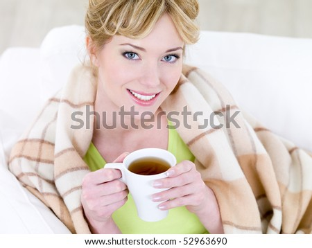 Portrait of young beautiful smiling woman with hot cup of coffee - high angle - stock photo