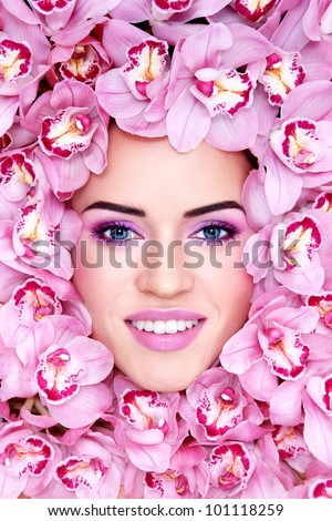 Portrait of young beautiful smiling woman with stylish make-up and pink orchids around her face - stock photo