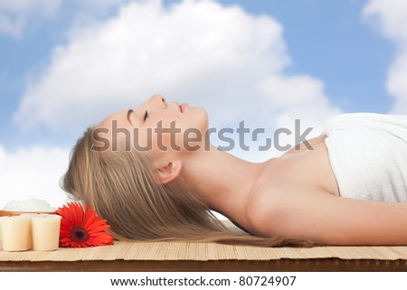Portrait of young beautiful spa woman with flower lying on bamboo mat against sky