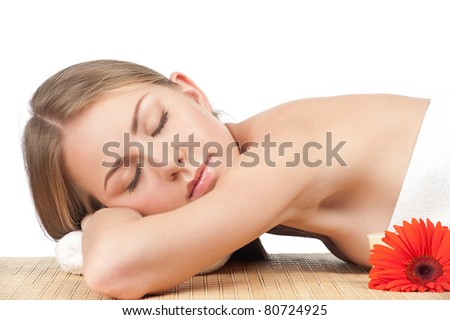 Portrait of young beautiful spa woman with flower lying on bamboo mat at spa salon