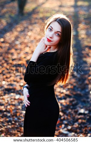 Portrait of young beautiful stylish girl in the park in sunset warm sunlight. Fashion style of smiling pretty girl in soft sunny daylight autumn, fall outdoor. Romantic woman in cozy sunset light.  - stock photo