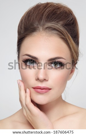 Portrait of young beautiful stylish girl with fancy hair bun and cat eye make-up - stock photo