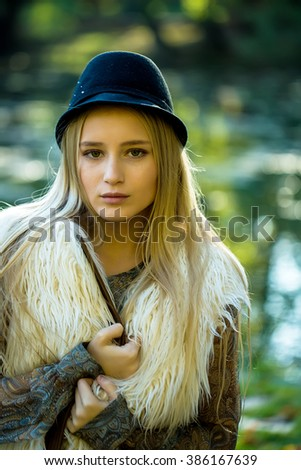 Portrait of young beautiful thoughtful woman with long blonde hair in stylish fur autumn waist coat and blue elegant hat outdoor on blurred natural background, vertical picture