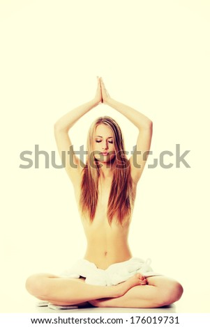 Portrait of young beautiful topless caucasian woman with towel on her waist practicing yoga - stock photo