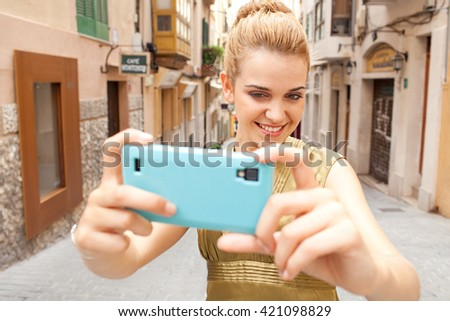Portrait of young beautiful tourist woman holding up a smart phone, taking selfies photos joyfully smiling in a destination city street on holiday, exterior. Woman using technology, travel lifestyle. - stock photo