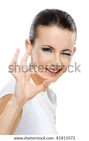 "Portrait of young beautiful winking dark-haired woman showing ""ok"" sign against white background. - stock photo"