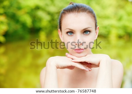 Portrait of young beautiful woman against lake in park.