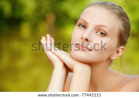 Portrait of young beautiful woman against lake in park. - stock photo