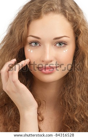 Portrait of young beautiful woman applying moisturizer cream on her face, isolated on white background - stock photo