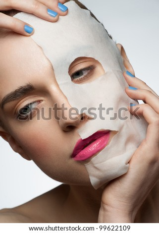 Portrait of young beautiful woman applying rejuvenating facial mask on her face - stock photo