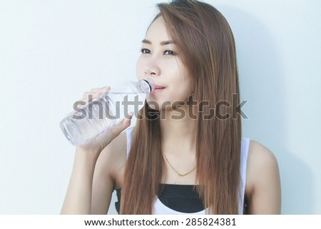 Portrait of young beautiful woman asia drinking water at summer and holding bottle - stock photo