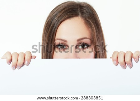 Portrait of young beautiful woman behind white blank board. Pretty girl holding paper card with copy space