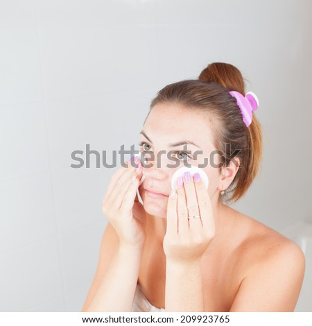 Portrait of young beautiful woman cleaning her face with cotton pads - stock photo