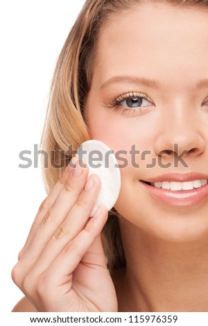 Portrait of young beautiful woman cleaning her face with cotton swab. Isolated on white background