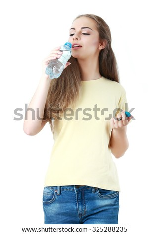 Portrait of young beautiful woman drink mineral water on white - stock photo