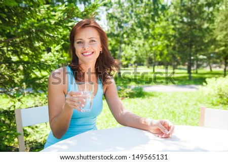 Portrait of young beautiful woman drinking water on picnic at summer green park. - stock photo