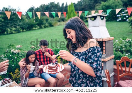 Portrait of young beautiful woman eating piece of cake and having fun in a outdoors summer barbecue with his friends - stock photo