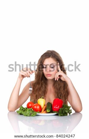 Portrait of young beautiful woman eating raw vegetables salad, sitting at the table, isolated over white background - stock photo