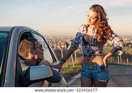 Portrait of young beautiful woman hitchhiker standing at side window and chating with car driver.