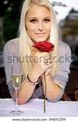 Portrait of young beautiful woman holding a red rose at a restaurant. - stock photo