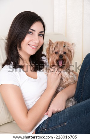 Portrait of young beautiful woman holding her dog